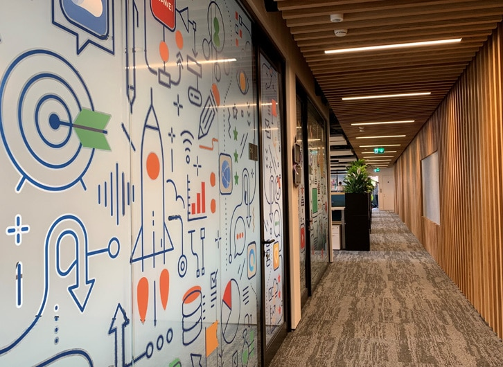 Printed window manifestations liven up this glass corridor