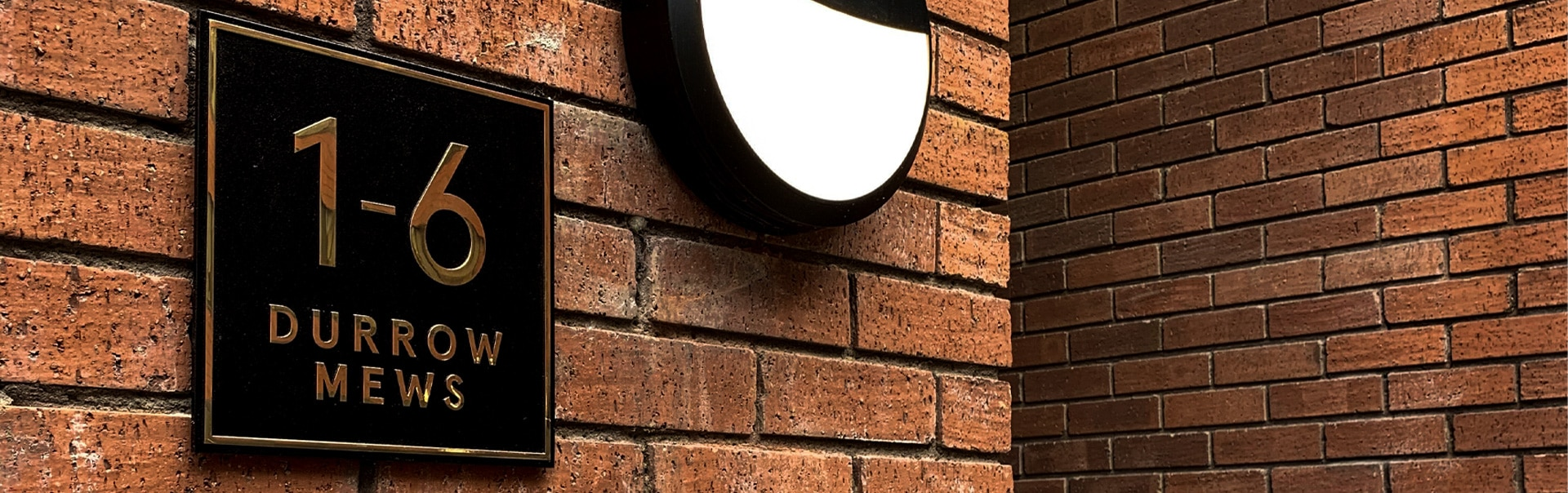 A wayfinding plaque in solid bronze gives this residential development an upmarket feel