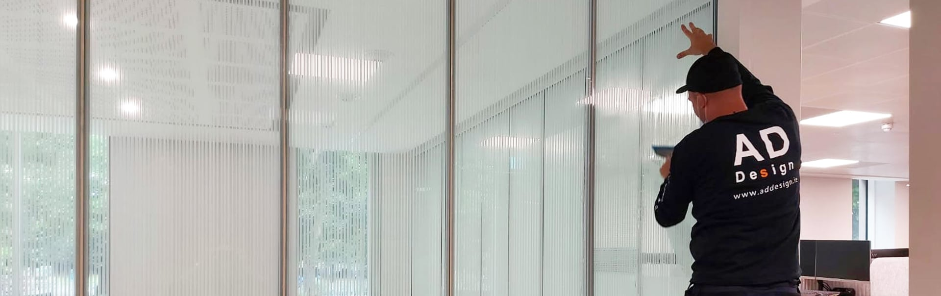 A specialist installer applies 3M Fasara window film to screen a new office