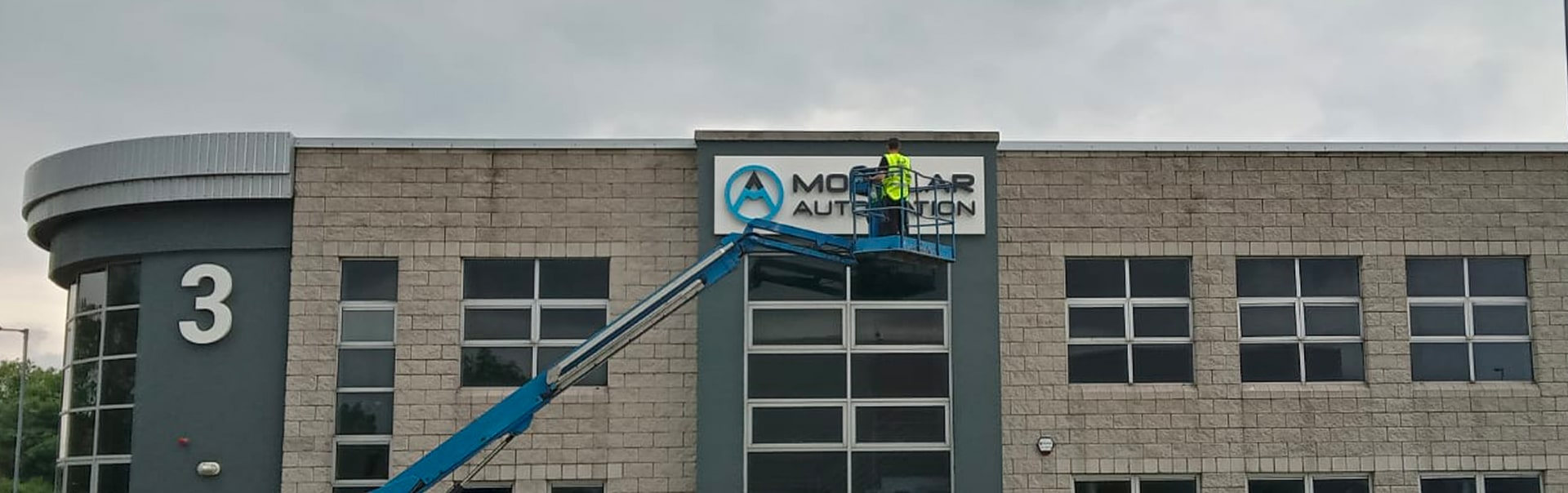 Working at height to install a halo-lit building sign at Modular Automation, Shannon.