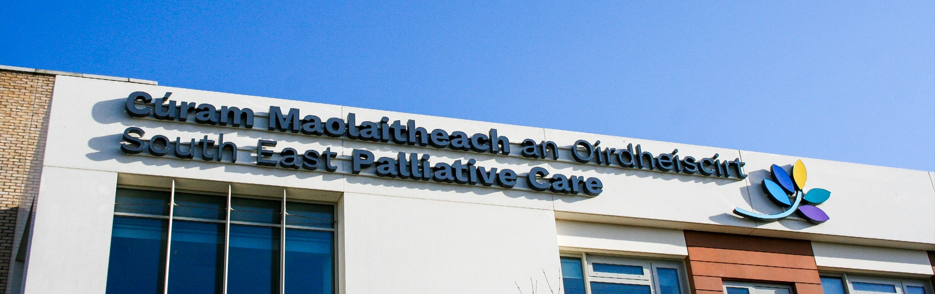 Face-lit skyline sign by day, University Hospital Waterford