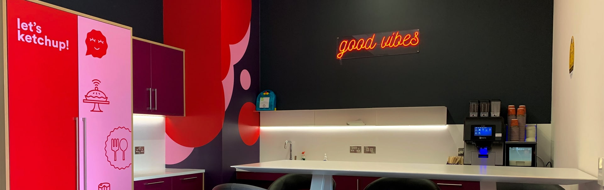 A faux neon sign and vibrant wall vinyls make this office kitchen pop
