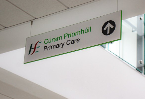 An overhead wayfinding sign points visitors to the reception at Bray Primary Care Centre