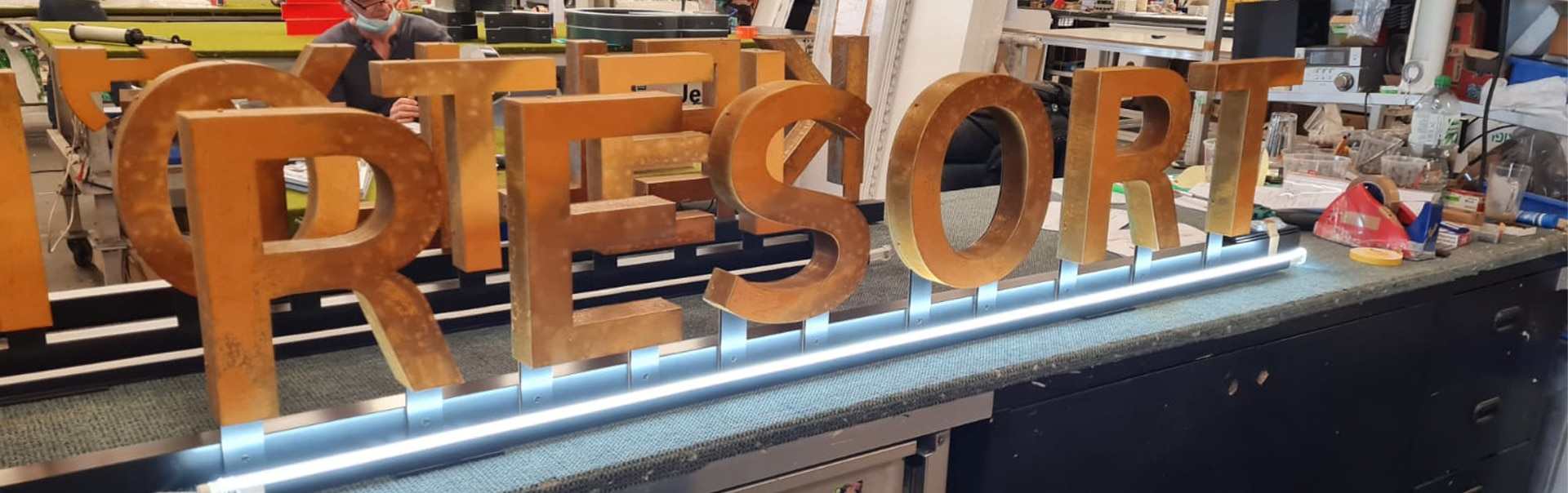 Sign fabricator applies the finishing touches to a corten steel canopy sign
