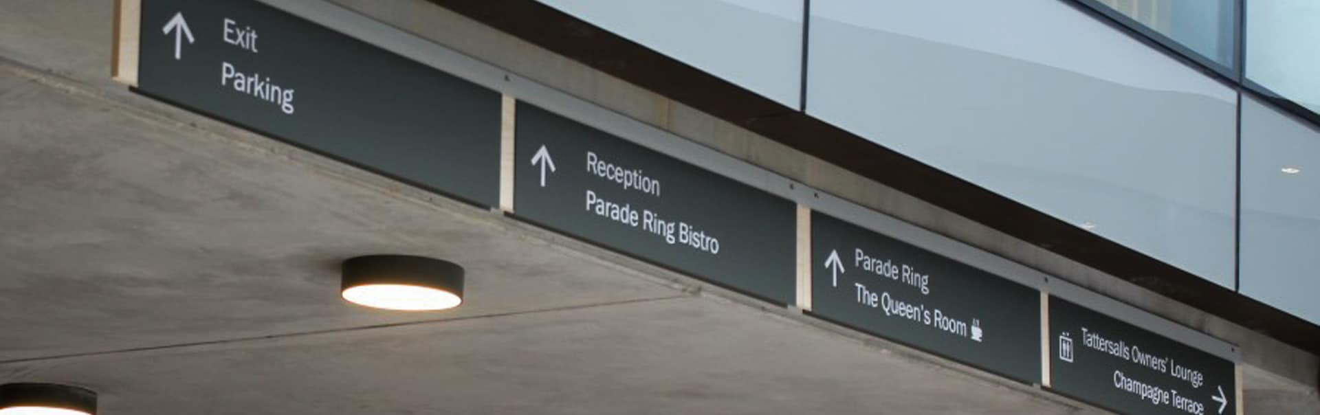A bank of overhead wayfinding signs helps racegoers to navigate the new stadium at The Curragh