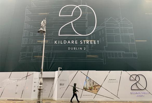 An office worker walks along the site hoarding at 20 Kildare Street