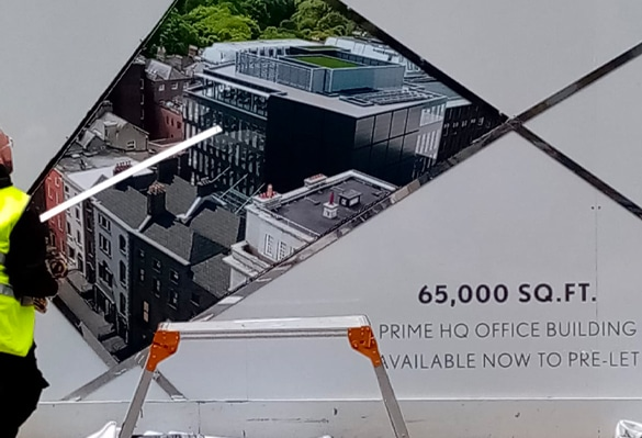 An installer applies chrome trims to a lightbox on the hoarding of 20 Kildare Street