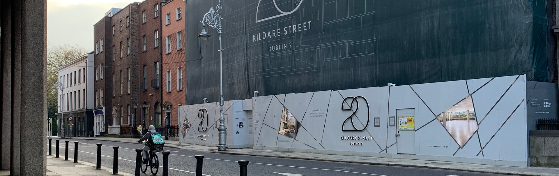 A Deliveroo rider passes the hoarding at 20 Kildare Street