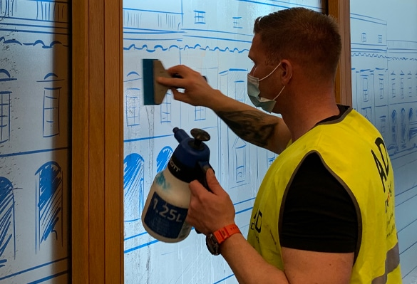 An installer applies optically clear glass manifestations to a meeting room window